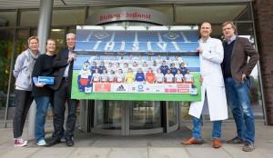Bildübergabe in der Blutspende, Dr. Sven Peine und ein HSV-Fanbeauftragter mit weiteren Personen